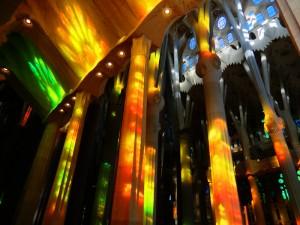 Die Sonne wirft Lichtreflexe der Kirchenfenster auf die Säulen im Innenberiech in der Farbe der Kirchenfenster von Gaudi in der Sagrada Familia